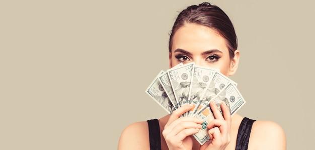 Ragazza con denaro contante in banconote in dollari. donna che tiene un sacco di soldi in valuta dollaro. concetto di lusso, bellezza e denaro.