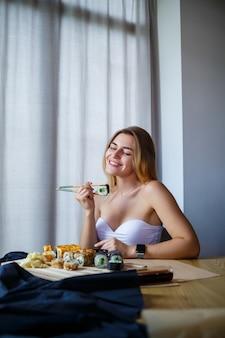 Rotolo di sushi delle bacchette della tenuta della ragazza. giovane donna che mangia sushi giapponese fresco delizioso.
