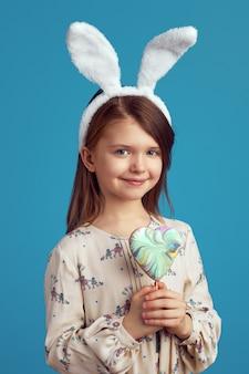Ragazza con un biscotto a forma di cuore che indossa orecchie da coniglio sul muro blu blue