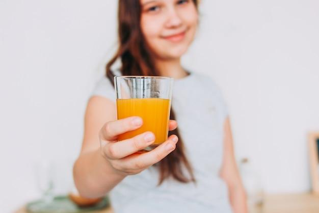 La ragazza che tiene vetro di succo d'arancia a disposizione, fuoco selettivo