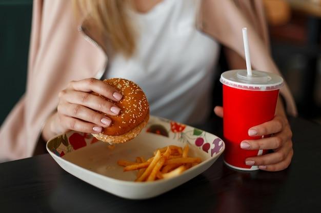 Ragazza che tiene un hamburger, mangiare fast food e bere cola
