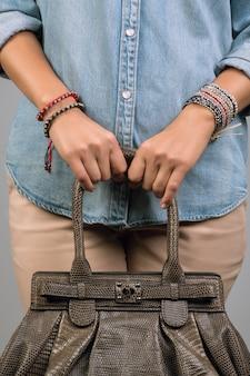 Ragazza con borsetta indossando bracciali