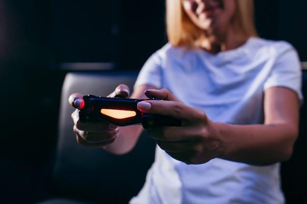 Ragazza che tiene in mano il gamepad e giocare ai videogiochi