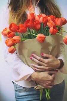 Ragazza con in mano un enorme mazzo di tulipani rossi