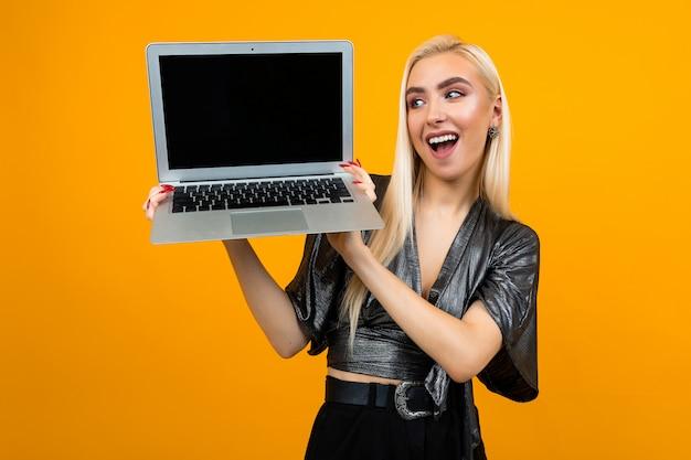 Laptop della tenuta della ragazza con lo schermo in bianco per la pagina web su fondo giallo