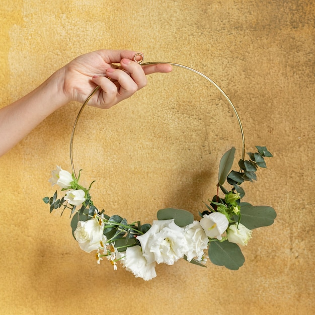 Ragazza con in mano una cornice rotonda dorata decorata con foglie
