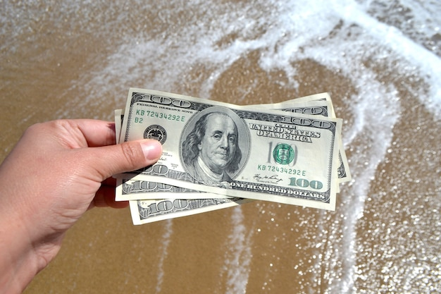 Ragazza con una banconota di 300 dollari sullo sfondo delle onde dell'oceano del mare con schiuma bianca e primo piano della spiaggia bagnata di sabbia. vacanza di dollari di soldi dell'oceano del mare dell'onda della mano. concetto di finanza denaro vacanza in viaggio