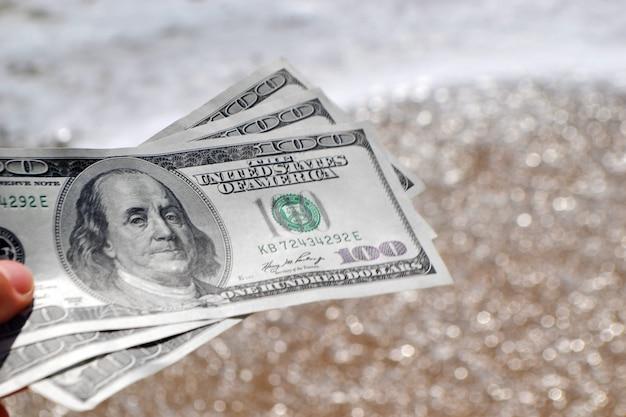 Ragazza con una banconota di 300 dollari sullo sfondo dell'oceano marino