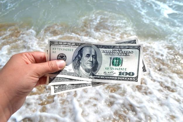 Ragazza con una banconota da 300 dollari sullo sfondo delle onde del mare