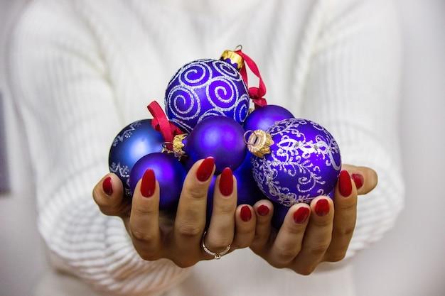 Ragazza con giocattoli, regali, orologi di capodanno nelle sue mani. concetto di natale.