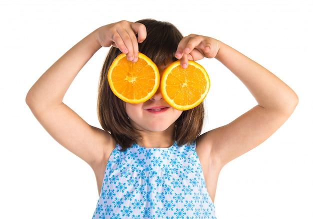 Ragazza che tiene fette d'arancia come occhiali
