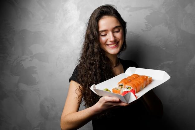 Ragazza con philadelphia rotoli in una scatola di carta su sfondo grigio. sushi, cibo a domicilio.
