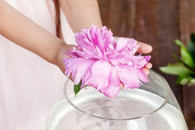 Ragazza che tiene in mano un fiore di peonia rosa. chiudere l'immagine