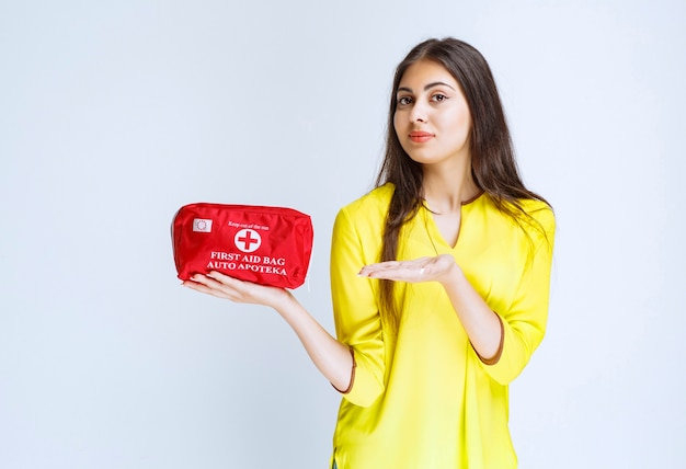 Ragazza che tiene e promuove un kit di pronto soccorso rosso.