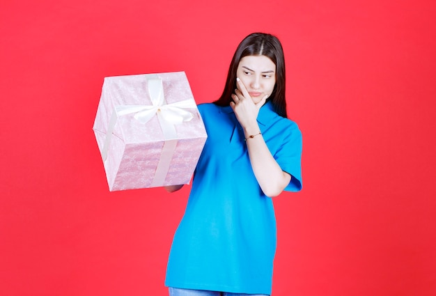 Ragazza con in mano una confezione regalo viola avvolta con un nastro bianco e sembra confusa e pensierosa.
