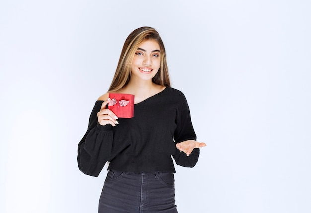 Ragazza con in mano una confezione regalo rossa e che chiama qualcuno per presentarla. foto di alta qualità