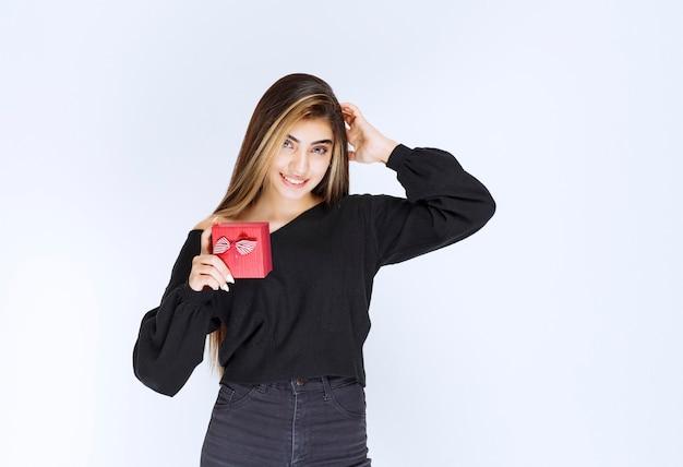 Ragazza che tiene una scatola regalo rossa e pensa o esita. foto di alta qualità
