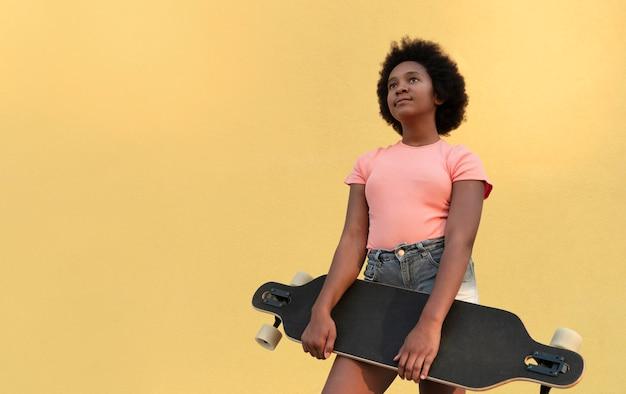 Ragazza con lo skateboard colpo medio