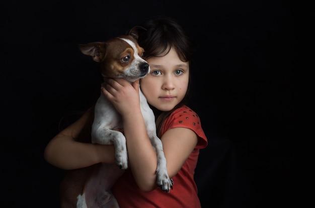 Ragazza con un piccolo cane nelle sue mani. migliori amici consept.