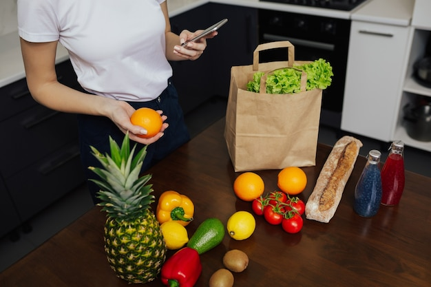 Ragazza con smart phone durante il disimballaggio del cibo dopo lo shopping