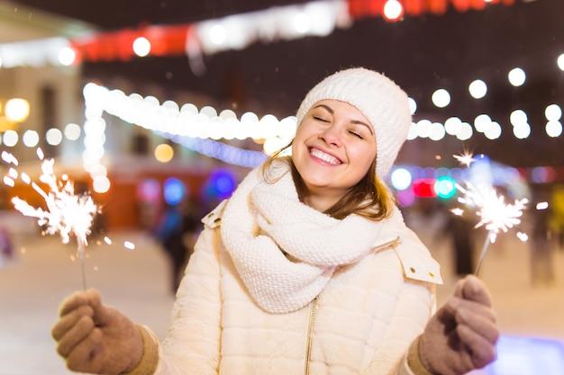 Ragazza con una stella filante in mano all'aperto inverno città sfondo neve fiocchi di neve