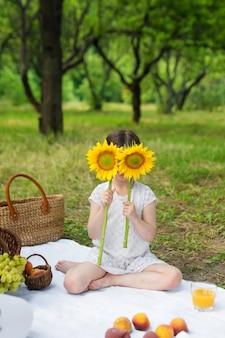Girasole della tenuta della ragazza davanti al fronte all'aperto. festa all'aperto in giardino, picnic.