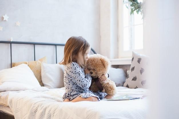 Ragazza con un orsacchiotto di peluche sul letto a natale