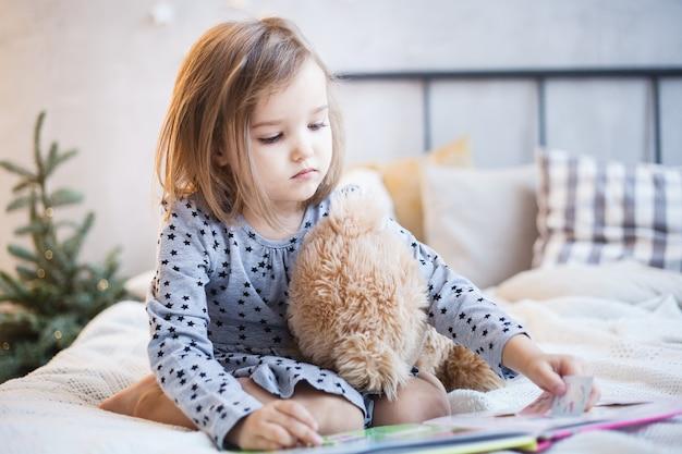 Ragazza con un orsacchiotto di peluche sul letto a natale Foto Premium