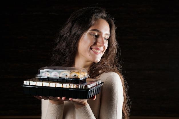 Ragazza con due scatole di sushi su sfondo nero