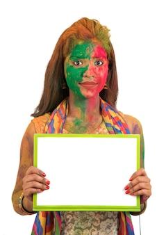 Ragazza con un cartello bianco con la faccia dipinta a colori in festival of colour holi. ritratto isolato