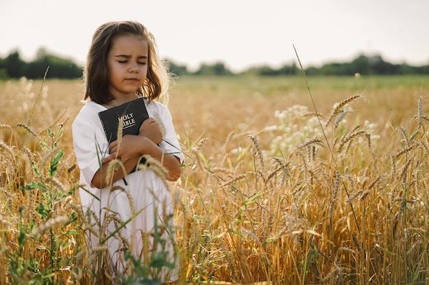 La ragazza tiene la bibbia nelle sue mani. leggere la sacra bibbia in un campo. concetto di fede, spiritualità e religione. pace, speranza