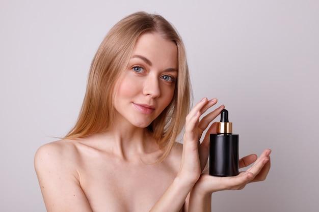 La ragazza tiene una camicia nera con cosmetici siero