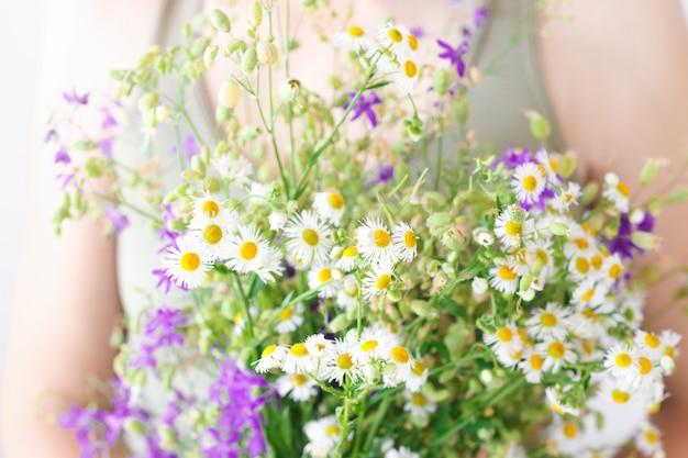 La ragazza tiene un bouquet multicolore colorato e fiori di campo e un primo piano di erba di prato