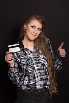 La ragazza tiene una carta di credito che sorride e mostra un gesto d'approvazione sfoglia su