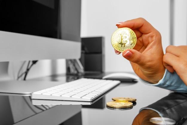 La ragazza tiene una cripta in bitcoin la sua mano su uno sfondo di laptop