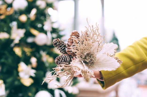 La ragazza tiene dei fiori decorativi nelle sue mani. sullo sfondo del bancone del negozio