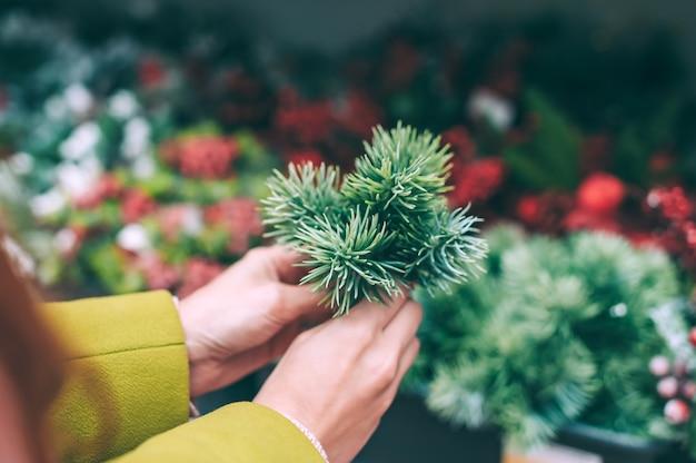 Una ragazza tiene in mano un ramo di abete per la decorazione di natale e capodanno.