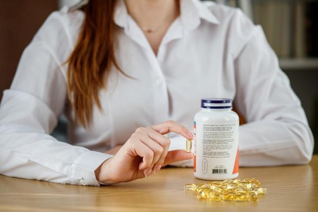 La ragazza tiene in mano una capsula di olio di pesce. capsule di omega-3 sul tavolo e in mano al medico.