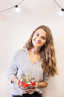 Una ragazza tiene in mano un florariumov, a forma di vetro con piante grasse, pietre e sabbia, decorato con nastri natalizi. regali di natale per casa e ufficio Foto Premium