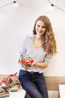Una ragazza tiene in mano un florariumov, a forma di vetro con piante grasse, pietre e sabbia, decorato con nastri natalizi. regali di natale per casa e ufficio