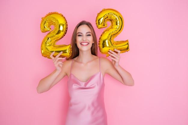 La ragazza tiene in mano palloncini di alluminio sotto forma di numeri con sconti del ventidue percento sulle vendite e cashback