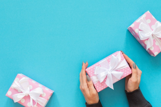 La ragazza tiene la confezione regalo, scatole regalo rosa a pois con nastro bianco e fiocco su sfondo blu, piatto laico, vista dall'alto, compleanno o san valentino