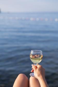Una ragazza tiene in mano un bicchiere di vino bianco sullo sfondo di un bellissimo mare blu. vacanza e concetto di vacanza. posto per un'iscrizione.