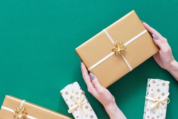 La ragazza tiene la confezione regalo in oro con fiocco, scatole regalo su sfondo verde
