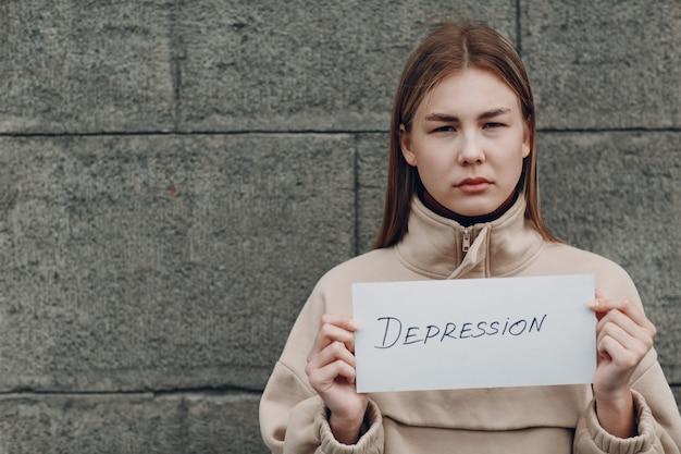 La ragazza tiene in mano il foglio di carta con la parola depressione.