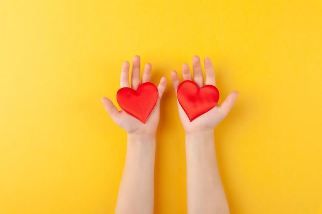 La ragazza tiene in mano cuori rossi, braccia di bambini, amore e concetto di san valentino, orizzontale, parete gialla, spazio copia, vista dall'alto, laici piatta