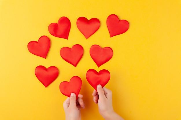 La ragazza tiene in mano cuori rossi, braccia di bambini, amore e concetto di san valentino