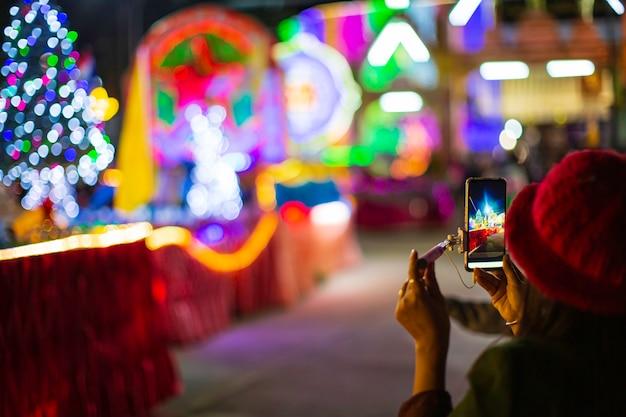 La ragazza tiene il dito davanti allo smartphone. sullo sfondo di un albero di natale con decorazioni festive