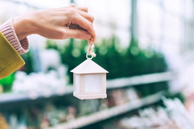 La ragazza tiene in mano una casa decorativa con decorazioni sull'albero di natale.