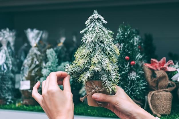 La ragazza tiene nelle sue mani un albero decorativo di natale, capodanno.